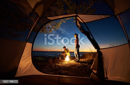 istock Young couple man and woman having rest at tourist tent and burning campfire on sea shore near forest 1002768222
