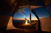 Camping on lake shore at sunset, view from inside tourist tent. Young romantic couple, man and woman preparing dinner on campfire on blue sea water background. Tourism, recreation and love concept.