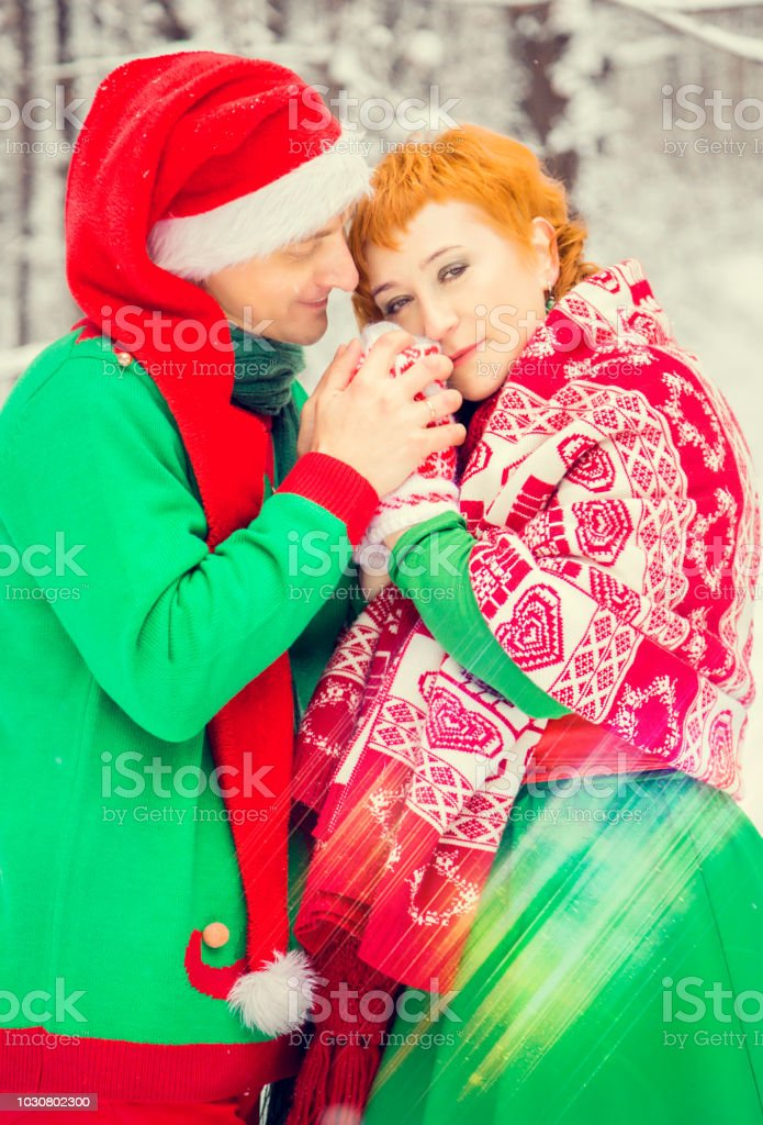 Young Couple Man And Woman Husband And Wife Are Walking In Costumes Of Flowers Typical Of The Elves Of Santas Helpers In A Winter Forest Under The