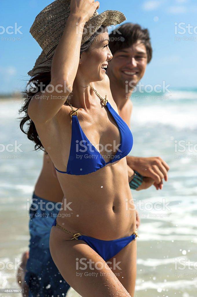 Pareja joven hombre y mujer jugando en el Surf en la playa - foto de stock