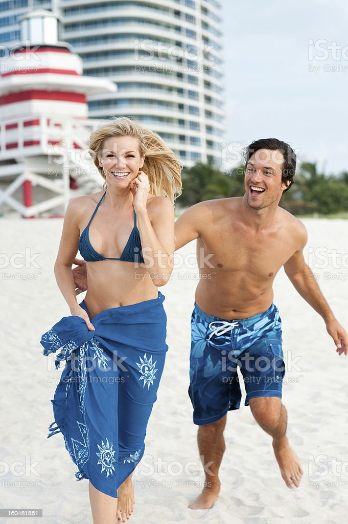 Young Couple Man and Woman Running on Beach royalty-free stock photo