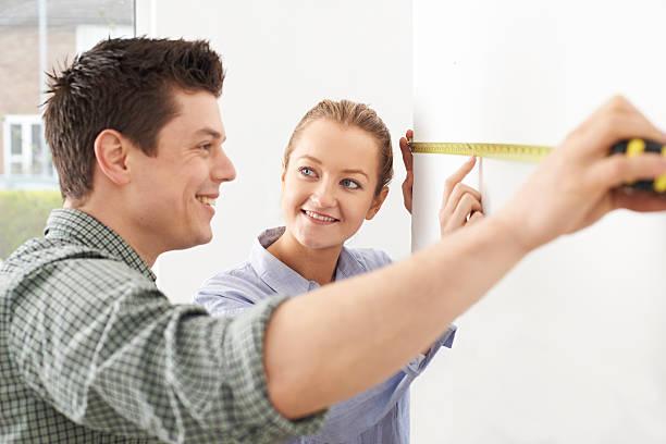 Pareja joven en pared de medición en Nuevo hogar - foto de stock