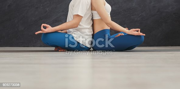 1060280760 istock photo Young couple meditating together, back to back 925273038