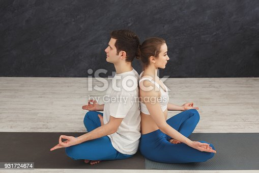 1060280760 istock photo Young couple meditating together, back to back 931724674