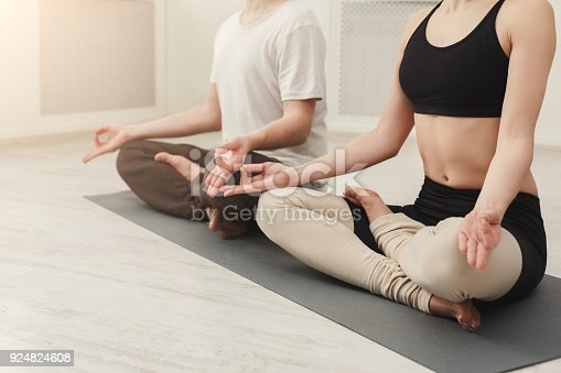 1060280760 istock photo Young couple meditating together in studio 924824608