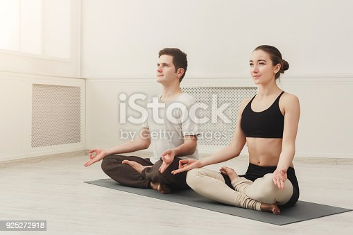 1060280760 istock photo Young couple meditating together in studio 925272918
