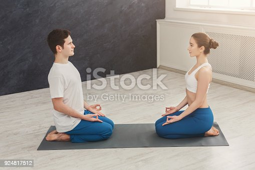 1060280760 istock photo Young couple meditating together, opposite each other 924817512