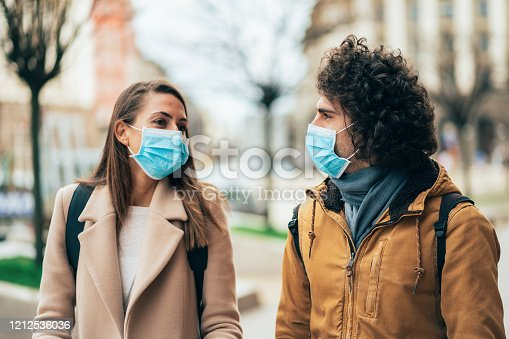 Young couple meet in quarantine outside on the city street wearing face protective mask to prevent Coronavirus and anti-smog