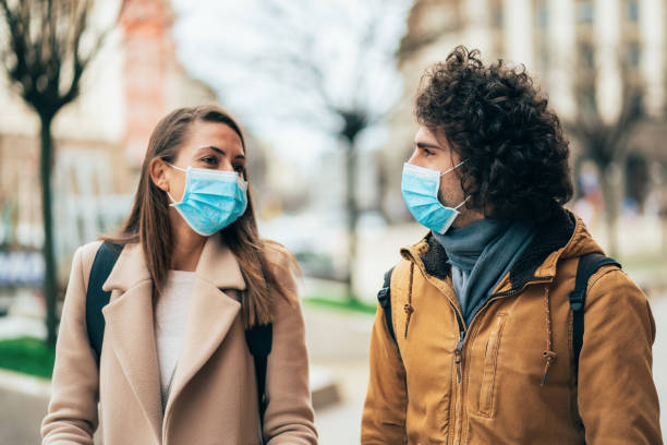 Young couple meet in quarantine Young couple meet in quarantine outside on the city street wearing face protective mask to prevent Coronavirus and anti-smog romantic activity stock pictures, royalty-free photos & images