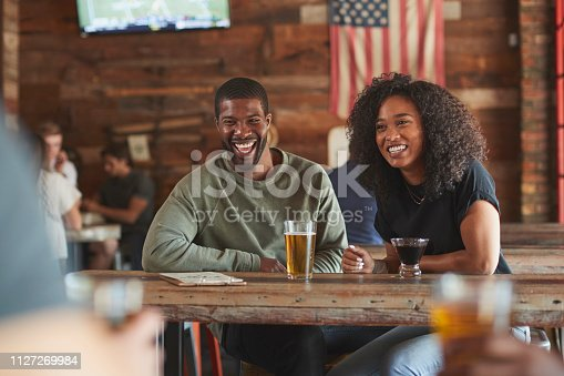 istock Young Couple Meeting In Sports Bar Enjoying Drink Before Game 1127269984