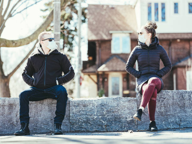 COVID-19, Young couple meeting outside Young couple wearing disposable face masks meeting in outdoors. Mask is Disposable Earloop Face Mask with Filters against Bacteria. social distancing stock pictures, royalty-free photos & images