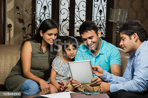 istock Young Couple meeting real-estate agent to buy property, presentation tablet - Stock image 1028463300