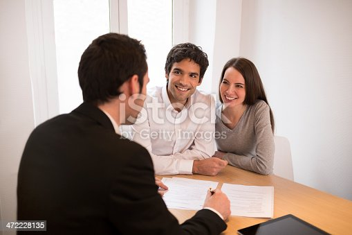 istock Young Couple meeting real-estate agent to buy property, presentation tablet 472228135