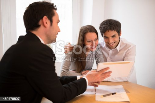 istock Young Couple meeting real-estate agent to buy property, presentation tablet 482478807