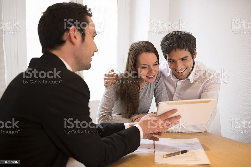 Jeune Couple réunion real-agent immobilier pour l'établissement, présentation tablette - Photo