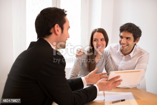 istock Young Couple meeting real-estate agent to buy property, presentation tablet 482479827