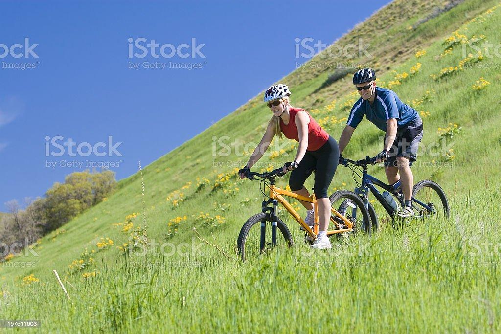 Young couple mountain biking through wildflower meadow royalty-free stock photo