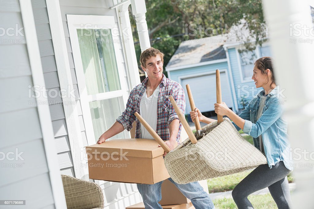 Young couple moving boxes and furniture into new home stock photo