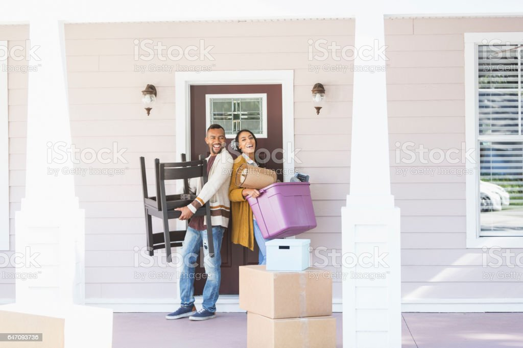 Young couple moving, carrying belongings thru front door stock photo