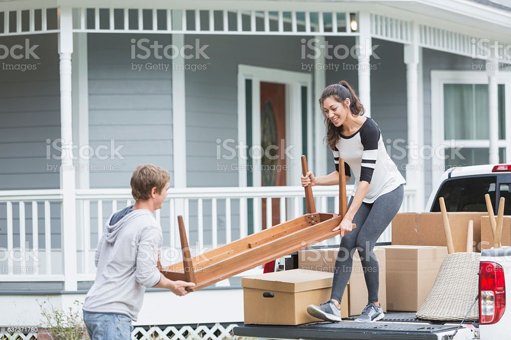 Young couple moving furniture into new home stock photo
