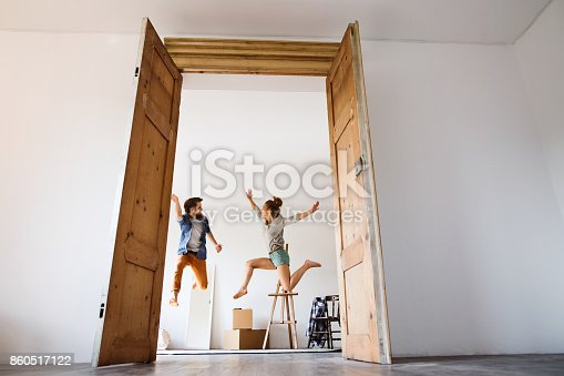 Young married couple moving in a new house, jumping up high.