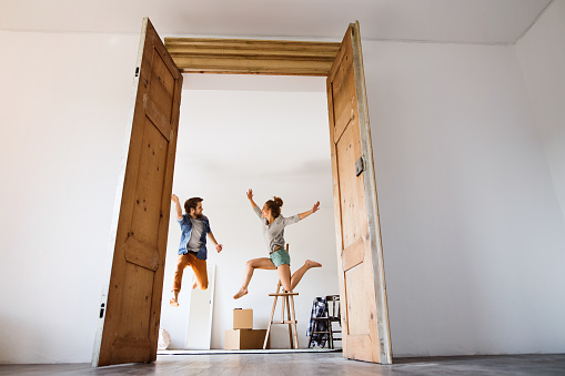 Young Couple Moving In A New House Jumping Up High Stock Photo - Download Image Now