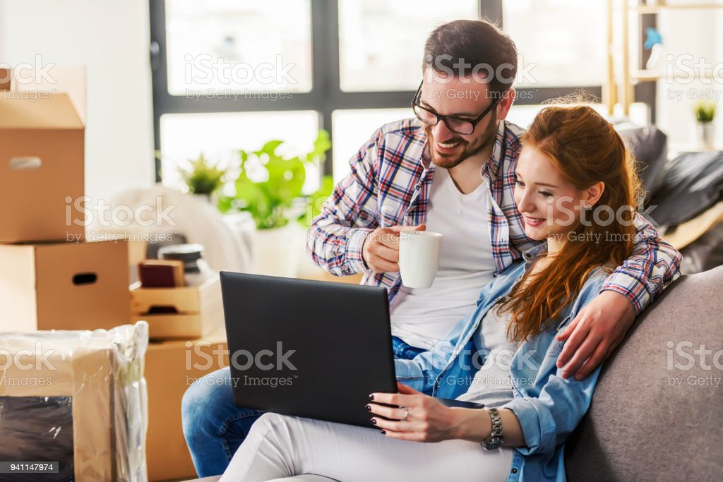Young couple moving in new home. Sitting and relaxing after unpacking. stock photo