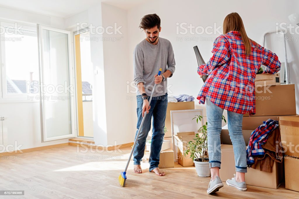 Young couple moving in new home. Unpacking box containers and cleaning. stock photo