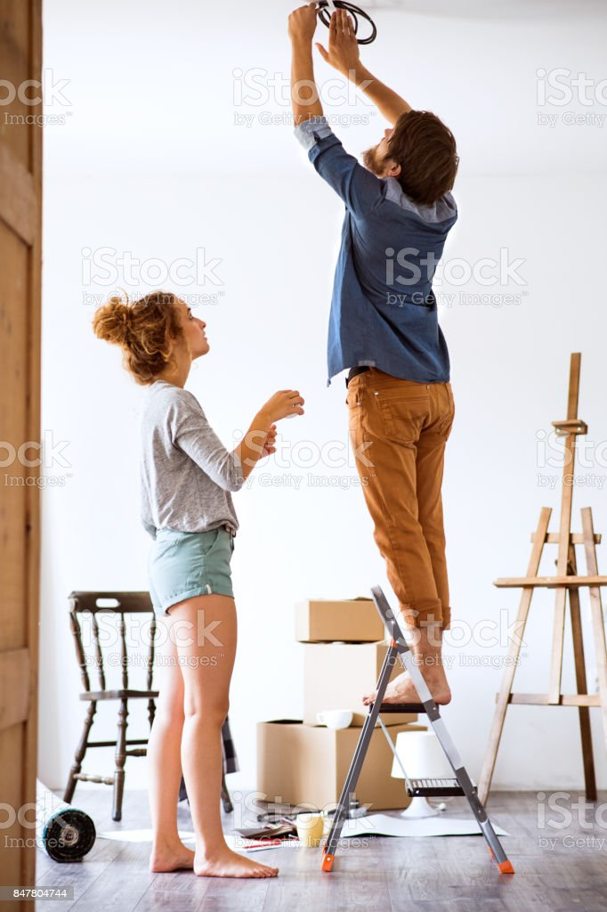 Young couple moving in new house, changing a light bulb. stock photo