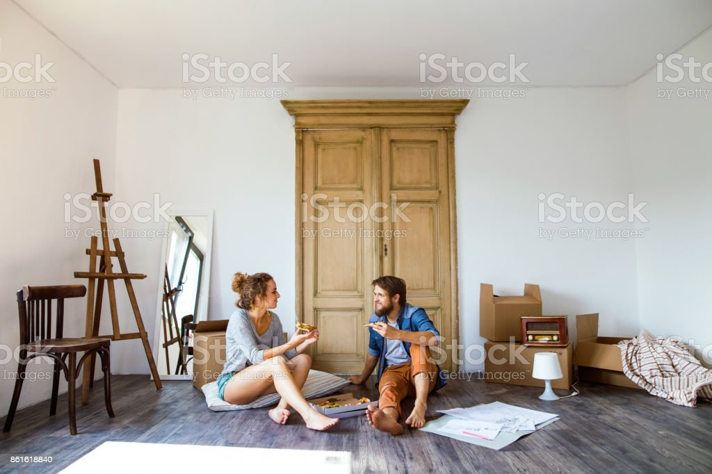 Young couple moving in new house, eating pizza. stock photo