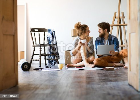 istock Young couple moving in new house, unpacking things. 861618426