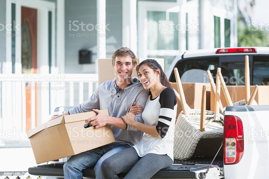 Young couple moving into new home, on pickup truck stock photo