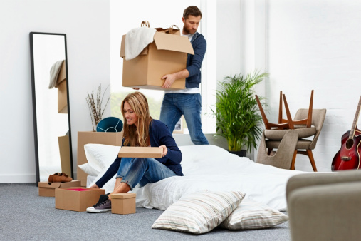 Young couple holding cardboard boxes moving into their new house