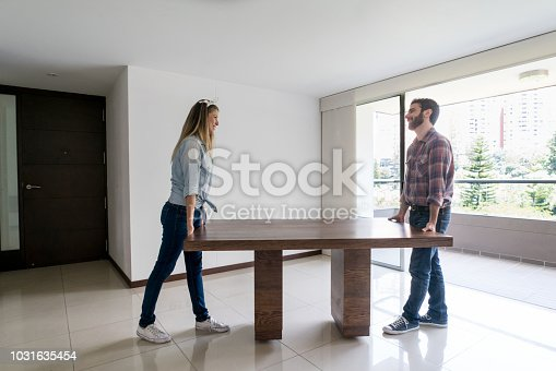 Young couple moving into their new place carrying a dining table while talking and having fun looking very happy