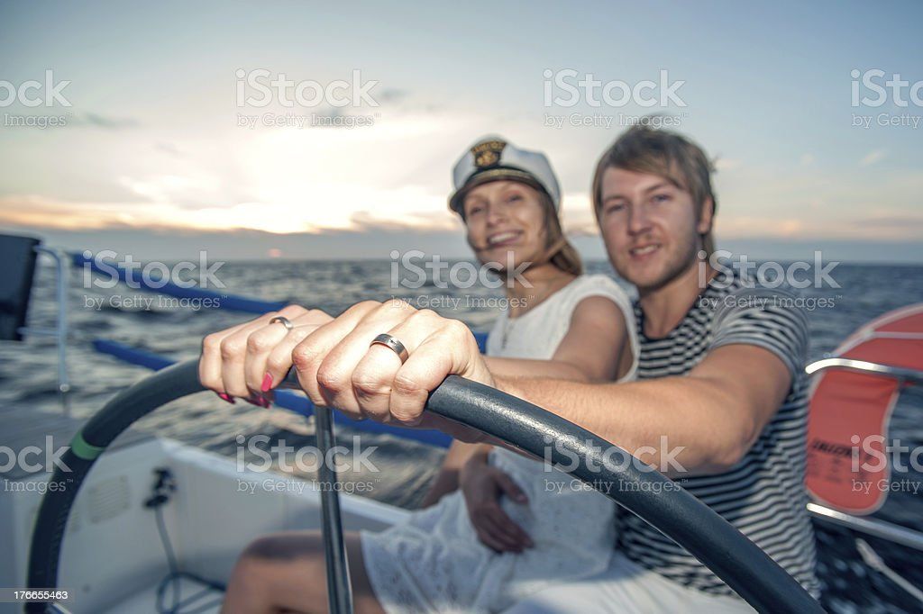 Young couple navigating on a yacht royalty-free stock photo