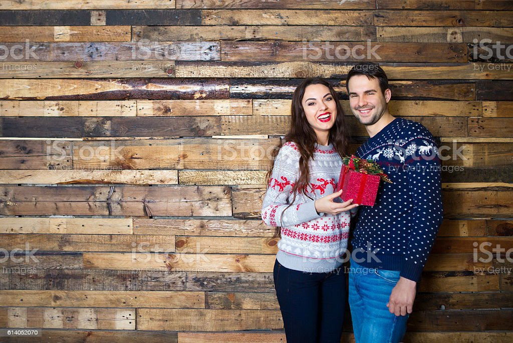 Young couple near wooden wall celebrating Christmas stock photo