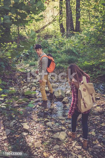 Young couple of sightseers enjoying a walk in the forest in a beautiful sunny day.