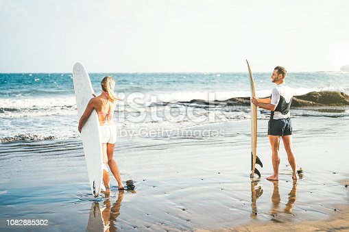 Young couple of surfers standing on the beach with surfboards preparing to surf on high waves - Sporty people having fun during a surfing day - Extreme sports, relationship and youth lifestyle concept