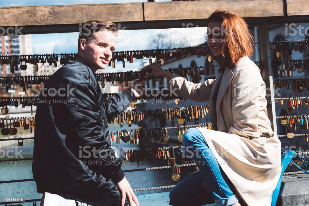 Young couple on a bridge locking a love lock stock photo