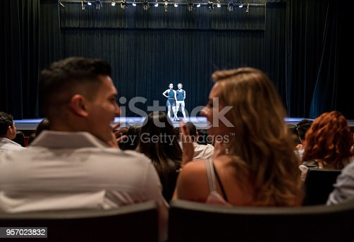 585298714 istock photo Young couple on a date at ballet applauding and looking at each other smiling 957023832