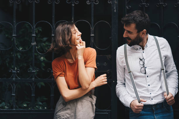Young couple on a date while standing by the fence. stock photo