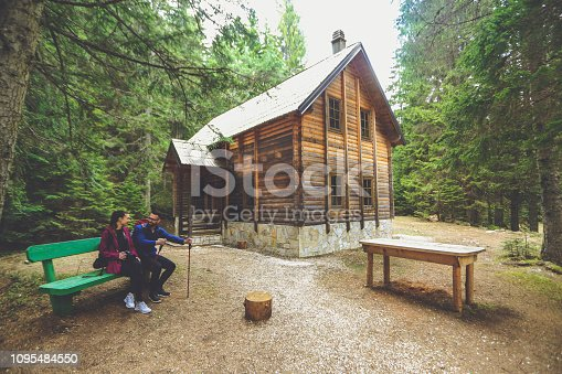 Young couple sitting on a park bench in front of a wooden cabin. Both Caucasian people.