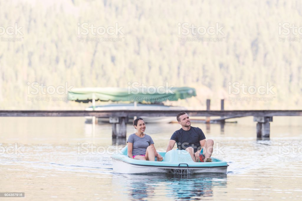 Pareja joven en un remo de barca de pedales alrededor del lago - foto de stock