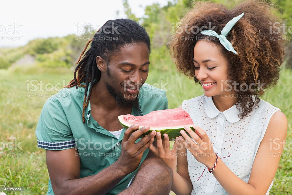 Young couple on a picnic eating watermelon stock photo