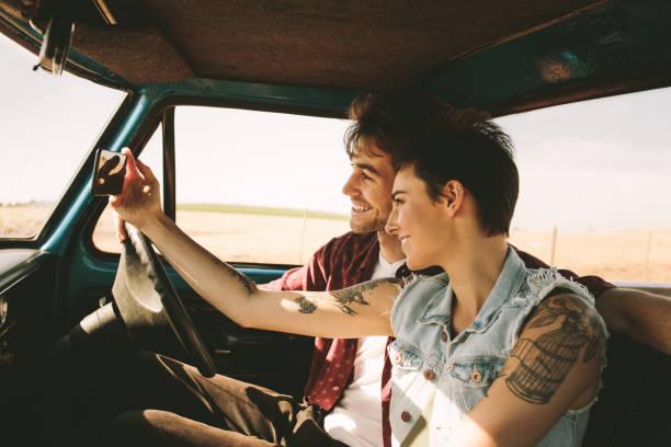 junges paar auf einer fahrt im auto fahren - freundin tattoos stock-fotos und bilder