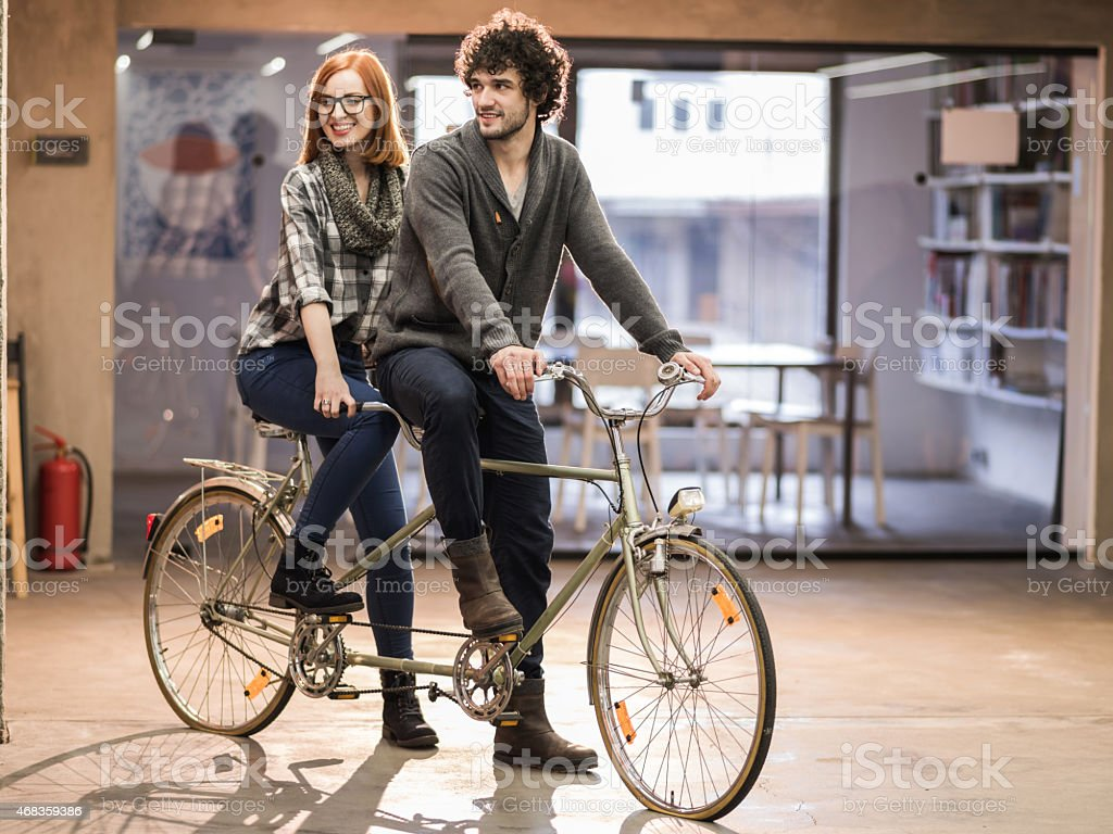 Young couple on a tandem bicycle indoors. royalty-free stock photo