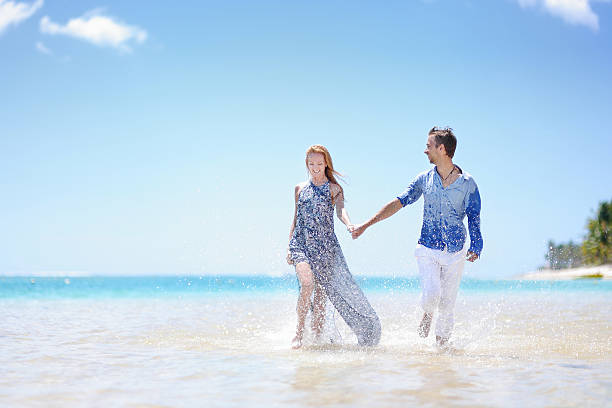 young couple on a tropical island - flitterwochen kleid stock-fotos und bilder