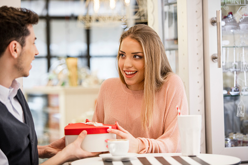 Young woman looking into her boyfriend eyes as he is giving her a gift, while they are sitting in cafeteria during the valentine's day