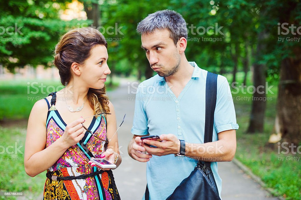 Beautiful happy couple together on a walk with their smart phones