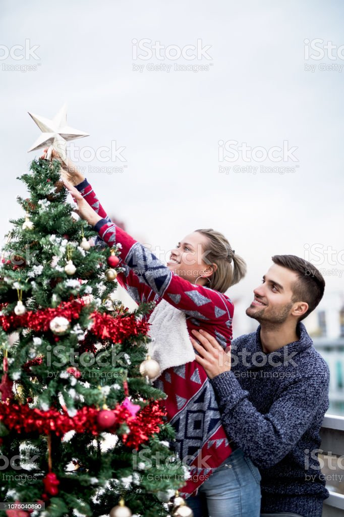 Young couple on balcony decorating Christmas tree stock photo
